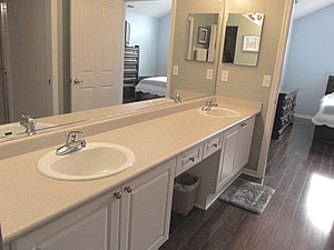 The Owner Suite Full Bathroom Also Has Pergo Flooring White Cabinetry With Vanity Seating Area Step In Shower 2 Sinks Linen Closet And Medicine Cabinet